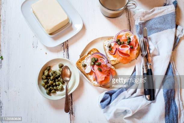 slices of toast with smoked salmon, caperberries, onion rings, and coffee - smoked food fotografías e imágenes de stock