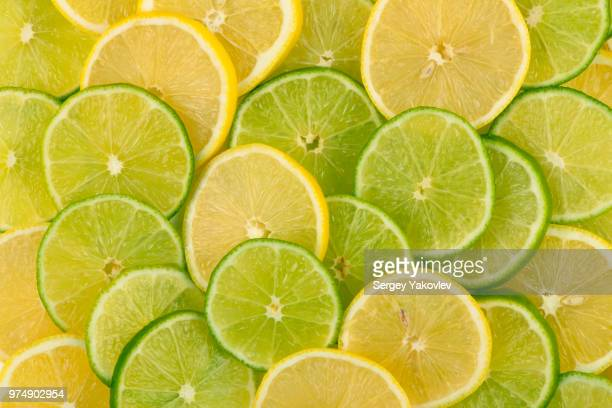 slices of yellow lemons and green limes - limette stock-fotos und bilder