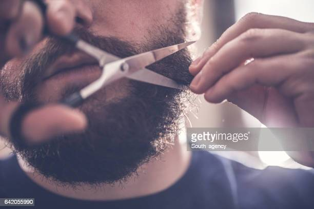 Tranchage barbe avec des ciseaux dans la salle de bain