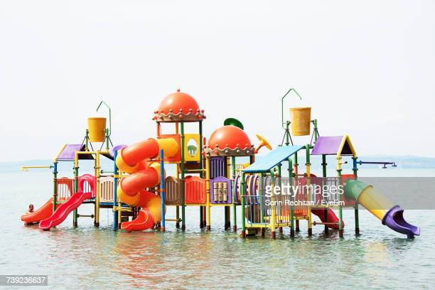 slide in lake against clear sky - slide play equipment stock pictures, royalty-free photos & images