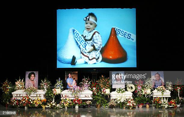 A slide show runs above four caskets containing five family members who were found shot to death in their home last week July 16 2003 in Bakersfield...