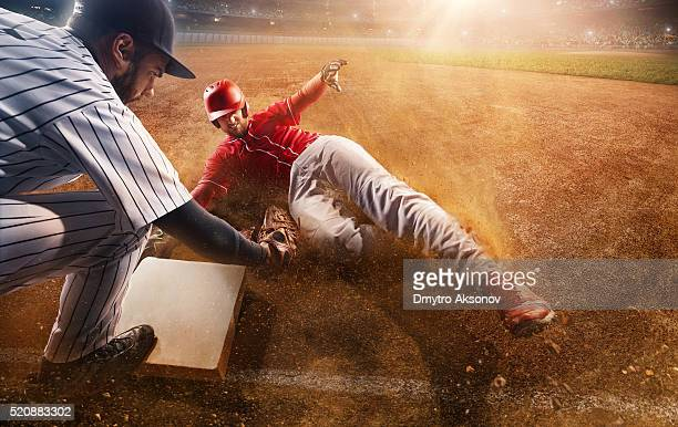 sliding and tagging on third base - baseball ball stock photos and pictures