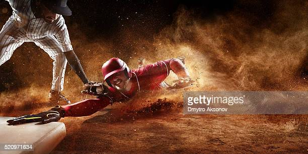 sliding and tagging on third base - baseball uniform stock pictures, royalty-free photos & images