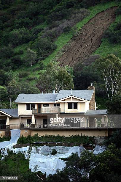Sliding mud both below and above a home in Chevy Chase Canyon is shown as southern California gets a break from the rains of the wettest season in...
