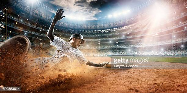 sliding on third base - baseballs stock photos and pictures