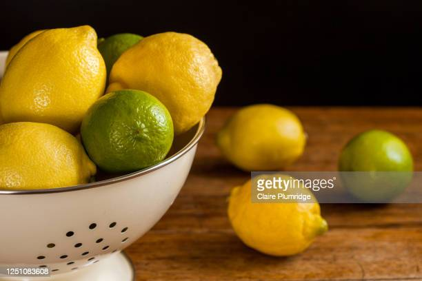 slightly cropped image of lemons and limes in a colander and some of the fruit by the side, on a wooden table with a dark background - newbury england stock pictures, royalty-free photos & images
