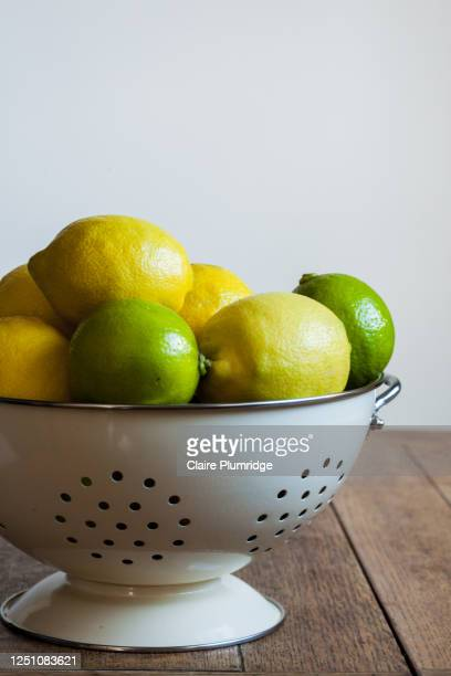 slightly cropped image of lemons and limes in a colander on a wooden table with a light background - newbury england stock pictures, royalty-free photos & images