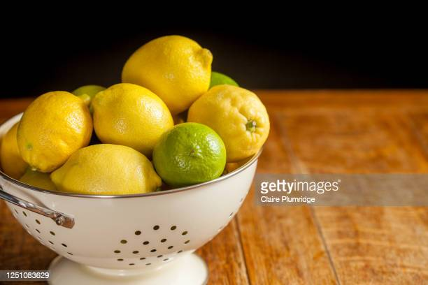 slightly cropped image of lemons and limes in a colander on a wooden table with a dark background - newbury england stock pictures, royalty-free photos & images