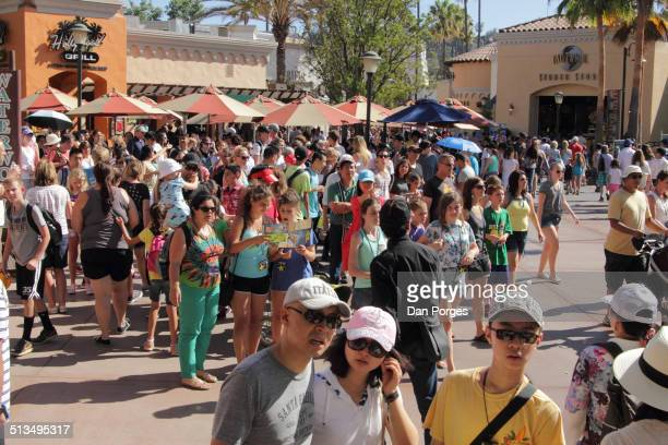 Slightly elevated view of a crowd of people they walk around Universal Studios Hollywood Los Angeles California July 21 2014