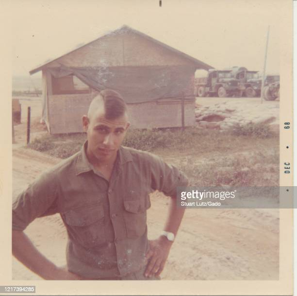 Slightly high angle shot of a young serviceman with a mohawk, looking up towards the camera, while standing on a dirt road on a sunny day, with a...