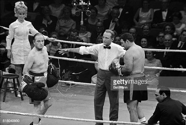 Slightly-bewildered Bob Hope is all set for a go at former world heavyweight boxing champ Rocky Marciano, as they stage a mock bout at the opening...
