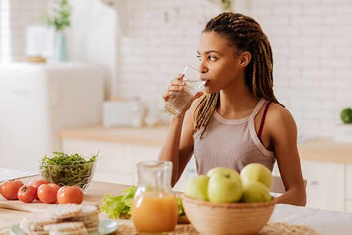 Slim and fit woman drinking water before having breakfast 1140193165