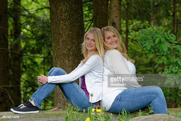 Slim and overweight woman sitting back to back at forest edge