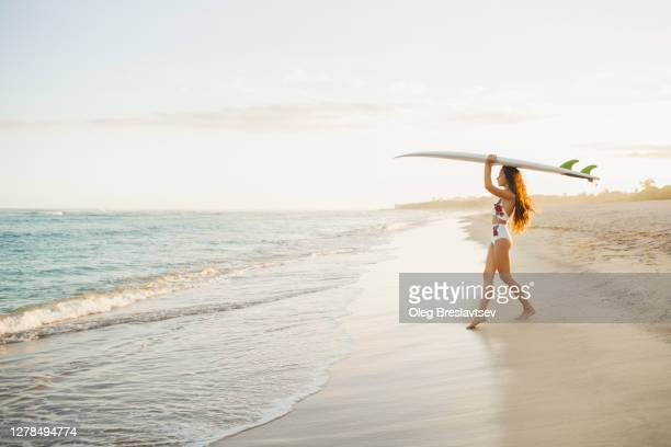 slim beautiful woman holding surfboard on beach. copy space and empty place on background. beach vacations in california. - california stock pictures, royalty-free photos & images