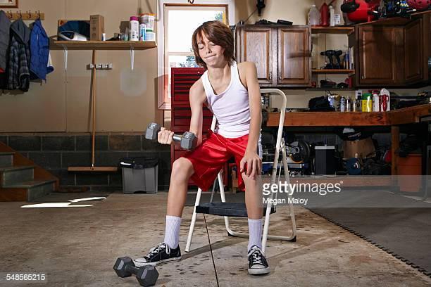 slim boy struggling to lift hand weight in garage - kids weightlifting ストックフォトと画像