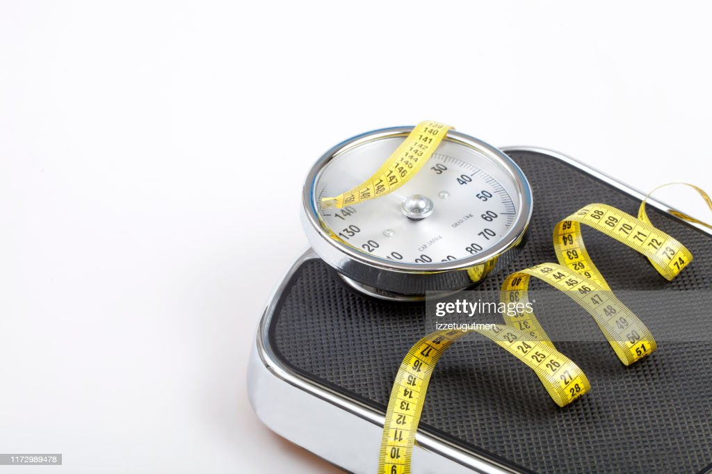 Slim concept with scale and measuring tape on white background top view : Stock Photo
