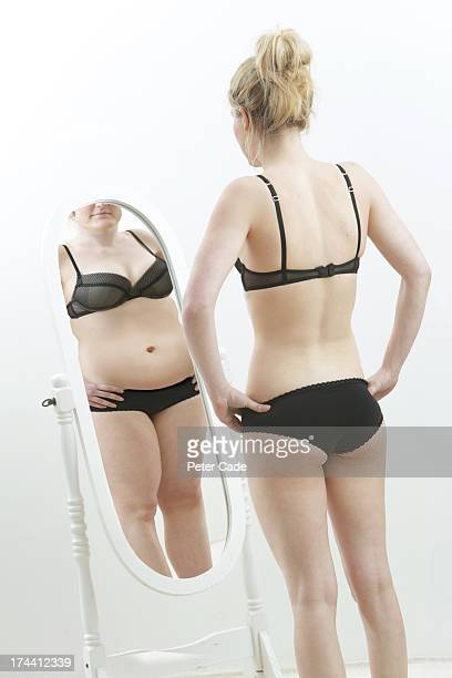 Slim girl looking at fat reflection in mirror