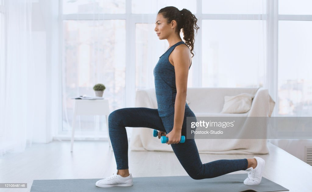 Slim Hispanic girl doing lunges with dumbbells at home, empty space : Stock Photo