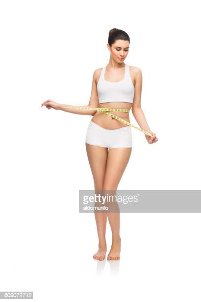 Slim femme latine tenant en mètre-ruban autour de taille
