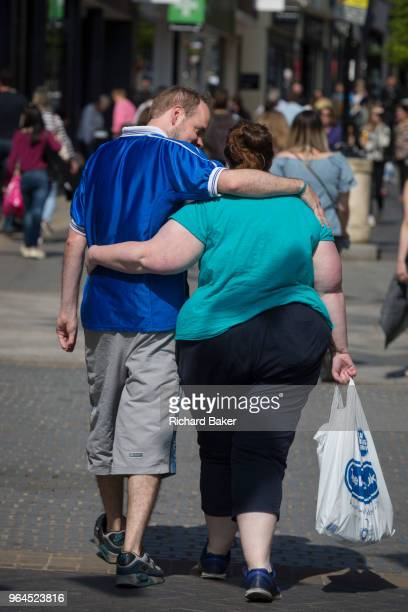 A slim man and obese woman walk through Windsor on 14th May 2018 in London England