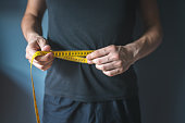 Slim man measuring his waist. Healthy lifestyle, body slimming, weight loss concept.