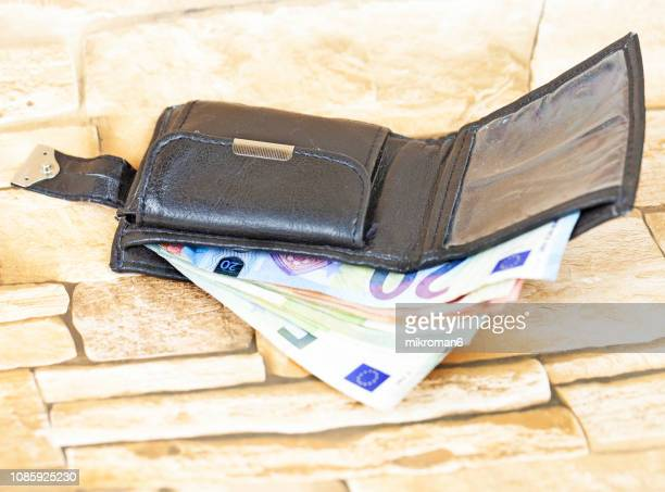 slim mens wallet, euro bills in a wallet - five euro banknote stock photos and pictures