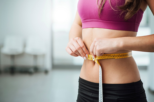 Slim woman measuring her thin waist 503865898