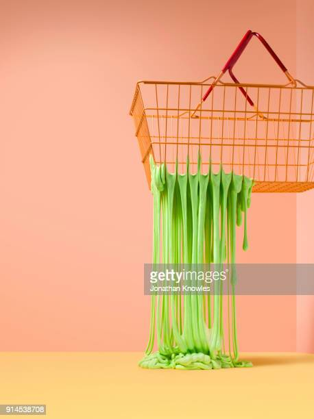 slime fripping through the holes in a wire shoping basket - slimy stock pictures, royalty-free photos & images