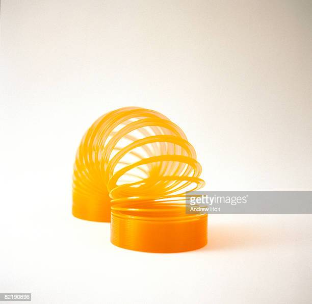 slinky - metal coil toy stock photos and pictures