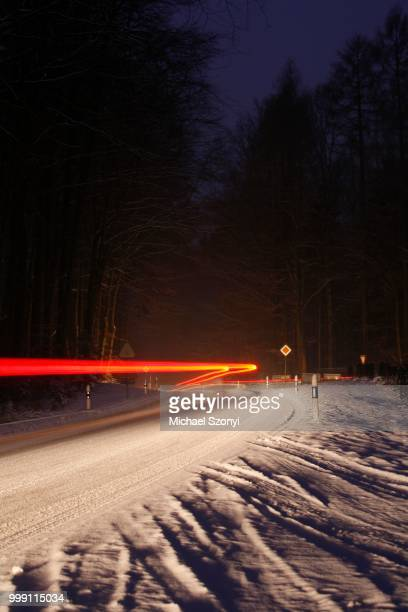 Slip hazard, hard-packed snow and black ice, bend on snow-covered road, car trails in winter