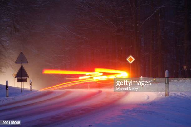 Slip hazard, hard-packed snow and ice, bend on snow-covered road, car trails in winter