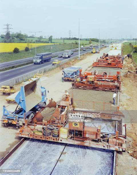 Slipform paving machines laying a road surface during widening works on the M1, showing concrete being tipped into the machine in the foreground....