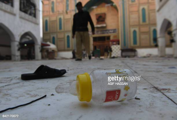 Slippers and a baby feeder of blast victims lie on the ground at the 13th century Muslim Sufi shrine of Lal Shahbaz Qalandar a day after a bomb...