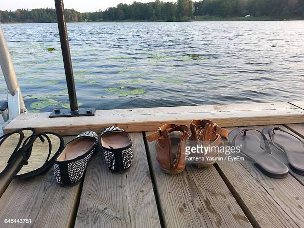 slippers and flat shoe on boardwalk against river - flat shoe stock pictures, royalty-free photos & images