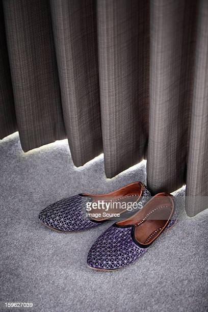 Slippers by a curtain