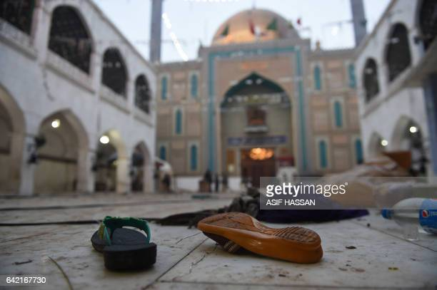 Slippers of blast victims lie on the ground at the 13th century Muslim Sufi shrine of Lal Shahbaz Qalandar a day after a bomb attack in the town of...