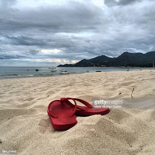slippers on sandy beach against cloudy sky - nikitina stock pictures, royalty-free photos & images