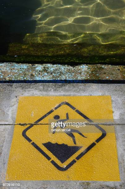 Slippery and uneven surface warning sign on concrete surrounding Towradgi Rock Pool in Towradgi, New South Wales, Australia