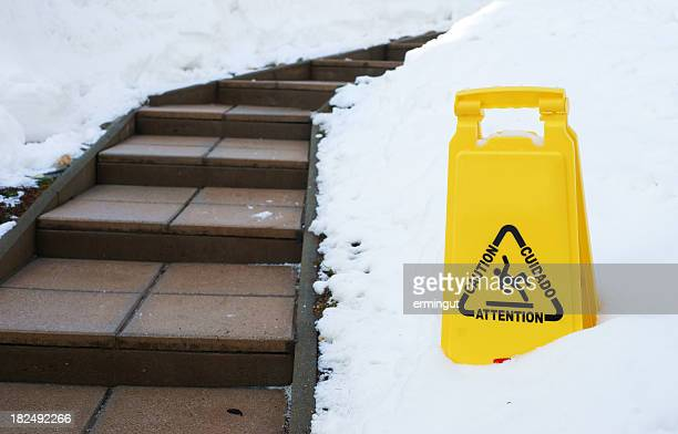 Slippery path in winter with caution sign