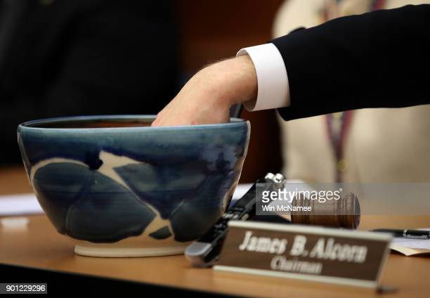 Slips of paper with the names of Virginia House of Delegates candidates Shelly Simonds and David Yancy are drawn from a bowl during a meeting of the...