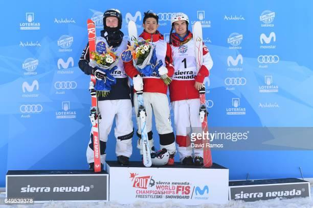 Sliver medalist Benjamin Cavet of France gold medalist Ikuma Horishima of Japan and bronze medalist Mikael Kingsbury of Canada pose during the flower...