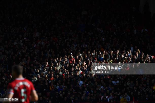 A sliver of light shines across the crowd during the English Premier League football match between Sheffield United and Liverpool at Bramall Lane in...