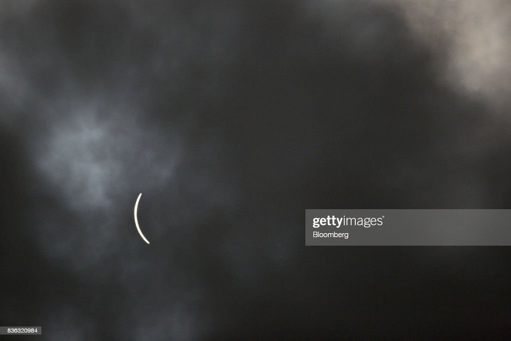A sliver of the sun remains visible through a passing cloud during a solar eclipse as seen from a viewing event on the campus of Southern Illinois University (SIU) in Carbondale, Illinois, U.S., on Monday, Aug. 21, 2017. Millions of Americans across a 70-mile-wide (113-kilometer) corridor from Oregon to South Carolina will see the sky darken as the sun disappears from view total during the eclipse, with Carbondale seeing totality for 2 minutes and 38 seconds. Photographer: Daniel Acker/Bloomberg via Getty Images