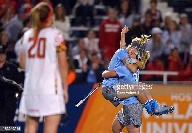 Sloane Serpe and Brittney Coppa of the University of North Carolina Tar Heels celebrate as Beth Glaros of the University of Maryland Terrapins...