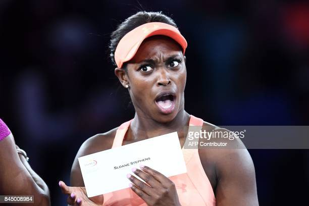 Sloane Stephens of the US reacts with her winning cheque after defeating compatriot Madison Keys during their 2017 US Open Women's Singles final...