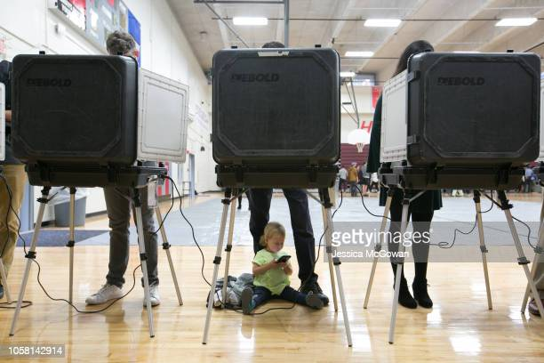 Sloane waits between her father's legs as he and other voters cast their ballots at a polling station set up at Grady High School for the midterm...