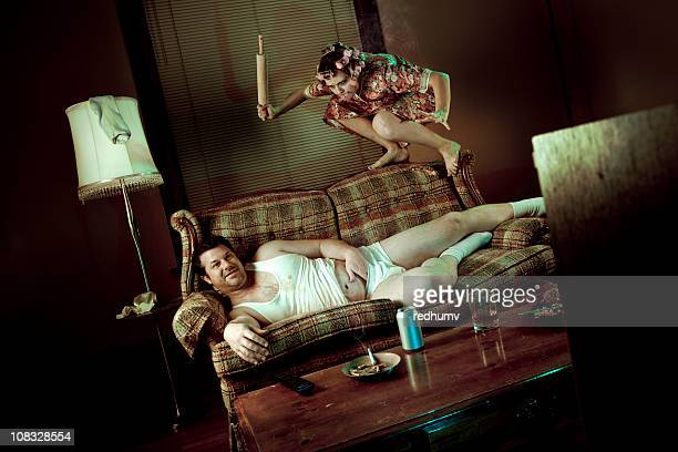 Slob Man watching television while woman pounces with rolling pin