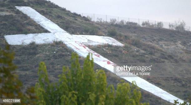 A slogan reading 'Stop 20N' painted by activists of Spanish feminist movement Femen is seen a giant cross lying on the hill above the cementery of...