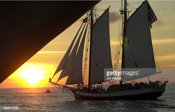 WEST FLA A sloop dwarfed by the hull of an snchored cruise ship sails into the sunset off Mallory Square Hundreds of tourists flock to the square to...
