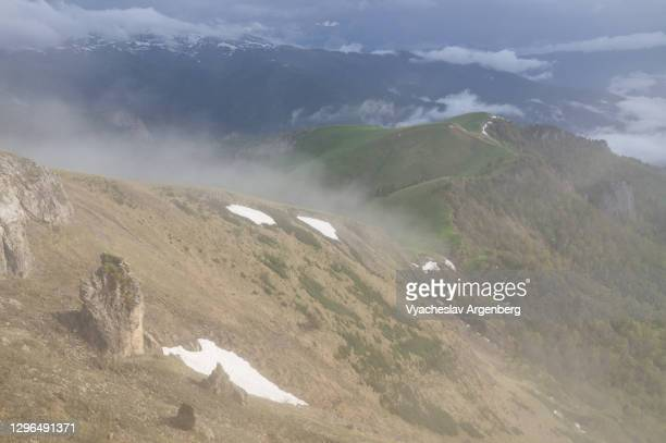 slopes of asbestnaya mount in clouds, early summer in caucasus mountains - argenberg stock pictures, royalty-free photos & images
